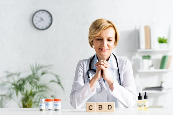 Happy-Doctor-In-White-Coat-Looking-With-CBD-Cubes-Lettering-Near-Bottle-With-Drugs